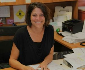 A female staff member sitting at her desk and smiling